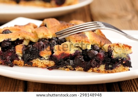 Piece of homemade lattice pie with whole wild blueberries in white plate with fork
