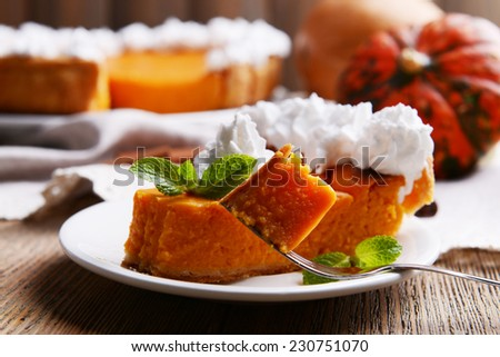 Piece of homemade pumpkin pie on plate on wooden background - stock photo