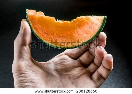 piece of juicy orange melon holds men's hand on a dark background - stock photo