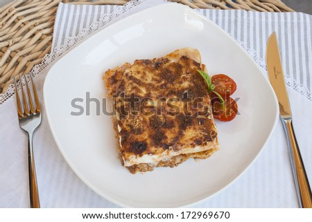 Piece of  lasagna accompanied with tomato cherry on white plate