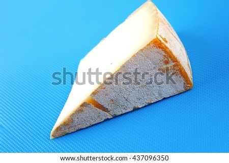 piece of light swiss cheese on blue board - stock photo