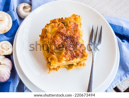 piece of meat lasagna with mushrooms in a white bowl, cutlery,  Italian food - stock photo