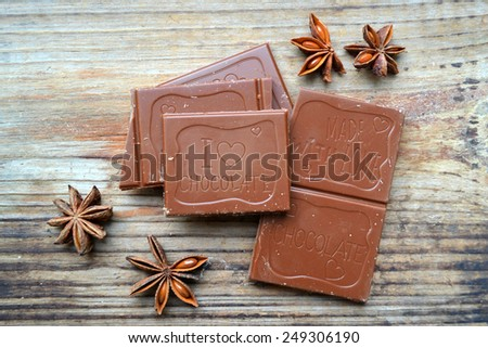 Piece of milk chocolate with star anise and cinnamon on wooden table - stock photo