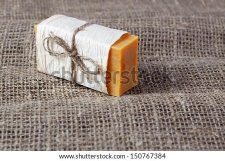 piece of natural soap, tied with twine on a linen cloth - stock photo