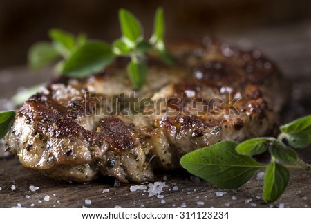 Piece of of grilled neck pork with herbs on an old wooden table - stock photo