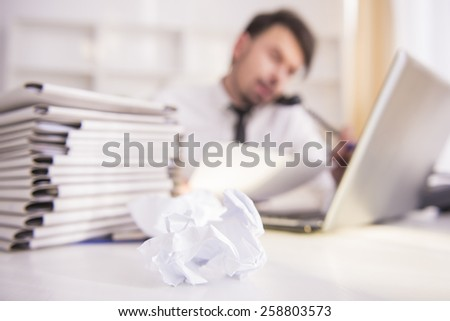 Piece of paper on focus. Blurred businessman on the background.