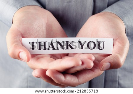 """Piece of paper with the words """"Thank you"""" in the woman's palms. - stock photo"""