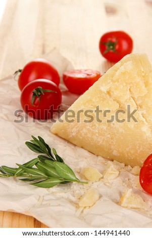 Piece of Parmesan cheese on paper on wooden table close-up - stock photo