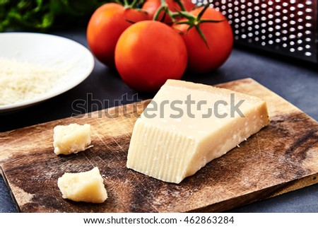 Piece of parmigiano reggiano cheese and grated parmesan cheese on wood board on stone background. Tomatoes and grater on back. Parmesan uses in pasta dishes, soups, risottos and grated over salads.