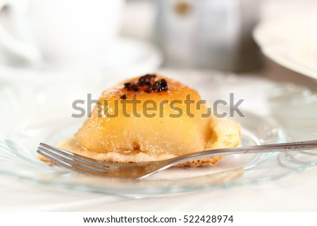 Piece of Pear Tarte Tatin with Cardamom at background Moka Pot and Coffee Cup
