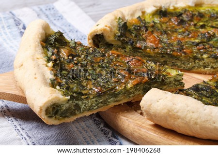 Piece of pie with green stuffed spinach, eggs and cheese close up on wooden board. horizontal   - stock photo