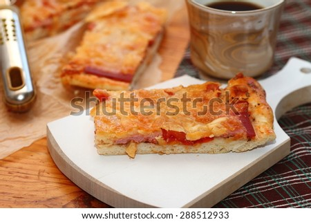 piece of pizza with sausage, tomatoes and three types of cheese