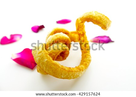Piece of Pork rinds or deep fried pork skin looks like gold a work of art on white background with pink rose petals:Close up,select focus with shallow depth of field. - stock photo
