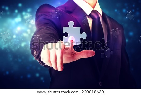 Piece of puzzle with businessman over blue tech background - stock photo