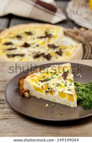 Piece of quiche lorraine on brown plate. Autumn setting