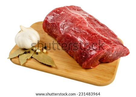 Piece of raw beef on a wooden board, decorated with garlic and bay leaves. - stock photo