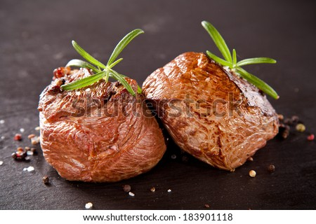Piece of red meat steaks with rosemary served on black stone surface. - stock photo
