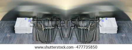 Piece of restaurant interior - cutlery and tissues (stacked napkins) on wooden table. Wide panoramic image. Copy space.