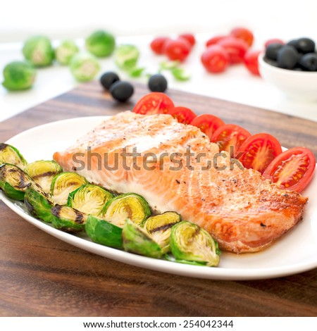 Piece of roasted salmon fillet with grilled brussels cabbage and tomatoes. Indoors still-life. Square image. - stock photo