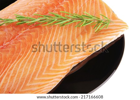 piece of salmon fillet on black plate over white and rosemary - stock photo