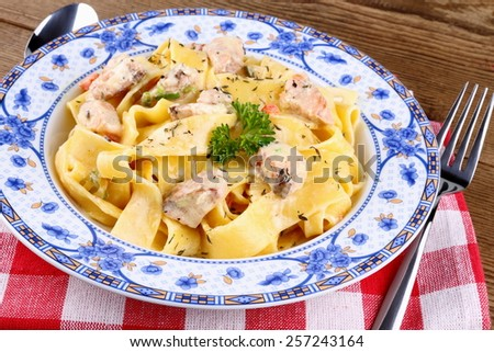 Piece of salmon fillet with tagliatelle, cream sauce, top view - stock photo