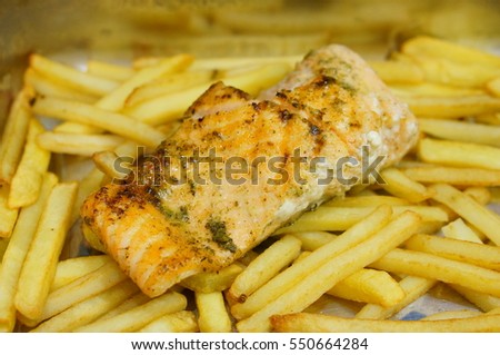 Piece of salmon on potato fries in soft focus