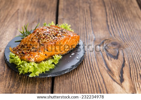 Piece of Smoked Salmon on wooden background (close-up shot) - stock photo