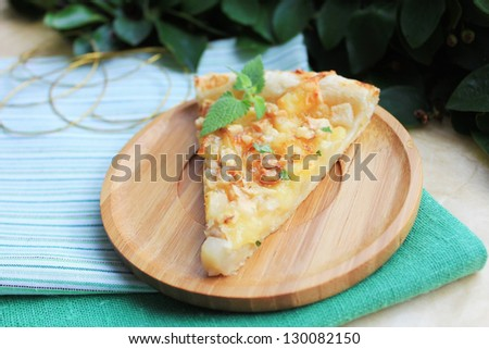Piece of snack puff pastry pie or quiche with camembert cheese, pear, walnuts and fresh mint on a wooden plate - stock photo