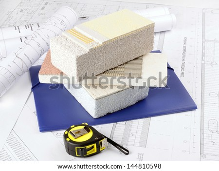 Piece of Styrofoam   with plaster, glue, net, polystyrene, thermal protection on  background  architectural drawings - stock photo