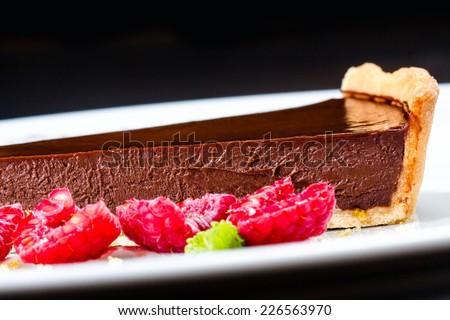 Piece of Sweet chocolate cake with fresh raspberries close up.   - stock photo