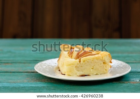 Piece of syrnik, light quark pie with apples on old wooden table painted turquoise - stock photo