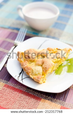 Piece of tasty biscuit apple pie and cup of hot cocoa