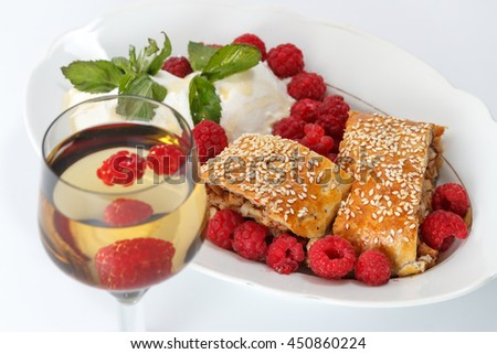 Piece of traditional apple strudel pie served with ice-cream, fresh mint, raspberry and glass of wine against white background, horizontal top view, close up