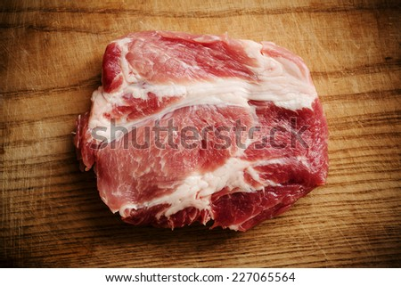 Piece of uncooked marbled steak or meat lying on a wooden counter in a kitchen or butchery, overhead view with copyspace