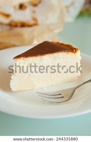 Piece of vanilla cheesecake with crashed biscuits on the top. Cheesecake was prepared with flour, white cheese, white sugar, vanilla sugar, eggs and butter. Presented on white plate. - stock photo