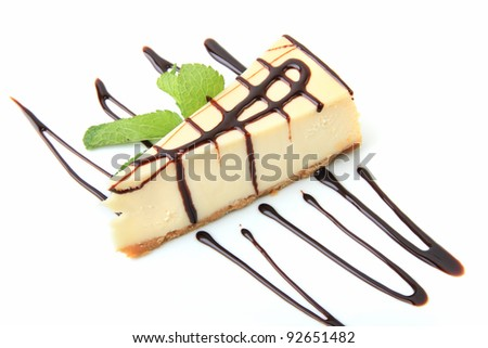 Piece of vanilla cheesecake with mint twig over white background - stock photo