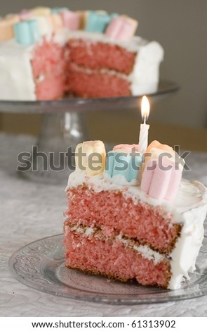 Piece of Whimsical Pink Cake with a Lit Candle - stock photo