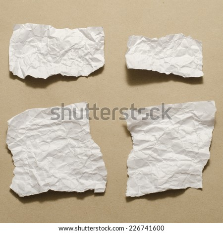piece of white crumpled paper on brown background - stock photo
