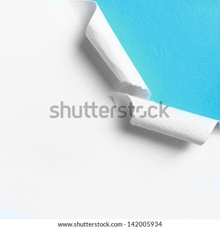 Piece of white paper with torn hole edge over blue background - stock photo