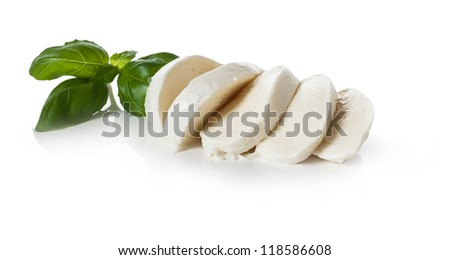 Piece of white, sliced mozzarella on white background decorated with basil - stock photo