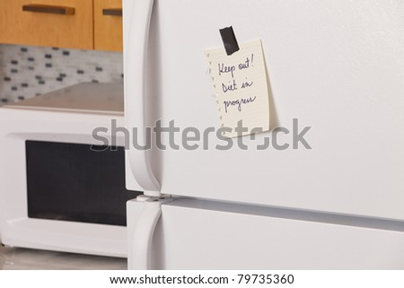 "Piece of yellow paper taped to a refrigerator door saying: ""Keep out! Diet in progress"" - stock photo"