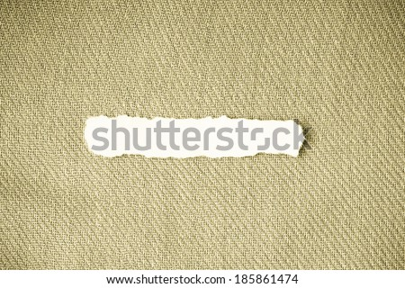 Piece scrap of white torn or ripped paper banner, blank copy space for text message on blue fabric textile material background - stock photo