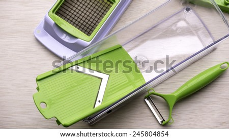 Pieces and set of stainless steel green color precision modern cutting food slicer or dicer for fruit, cheese, sausage and vegetables on wooden table surface with some room for text. - stock photo