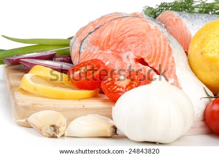 Pieces of a fresh salmon with vegetables on a white background