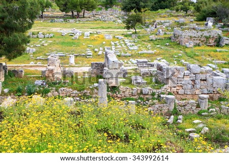 Pieces of ancient buildings scattered on the ground in ancient site of Corinth, Greece