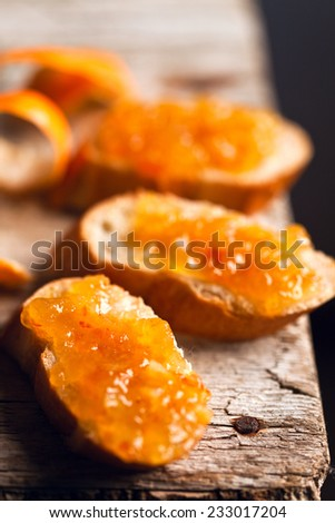 pieces of baguette with orange marmalade closeup on rustic wooden board - stock photo
