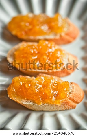 pieces of baguette with orange marmalade closeup on white plate - stock photo