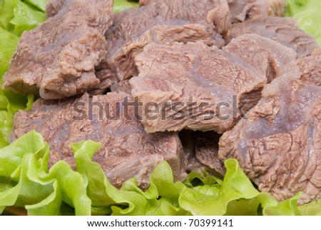 Pieces of boiled meat lay on salad leaves - stock photo