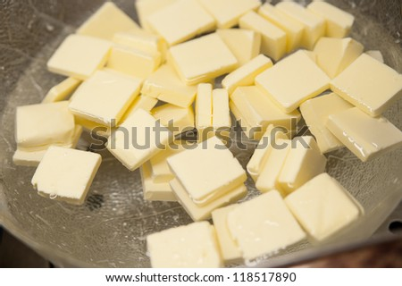 Pieces of butter in a bottle with water - stock photo