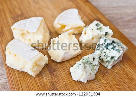 Pieces of camembert cheese and cheese with blue mold on a wooden board